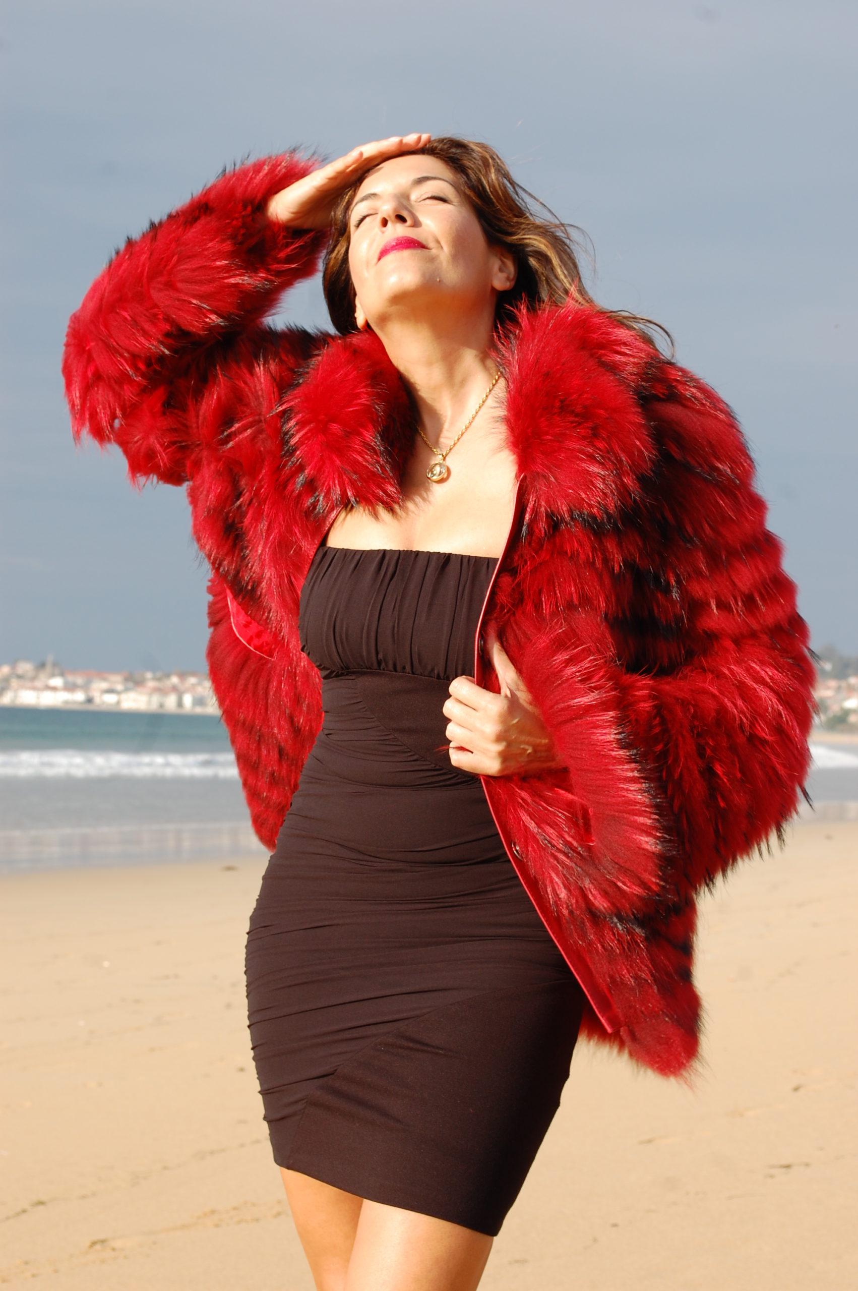 mujer 50 años en la playa con abrigo rojo
